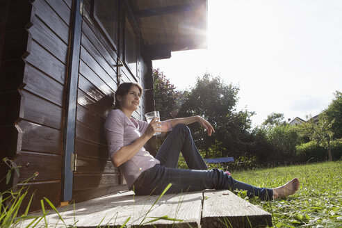 Smiling woman sitting at garden shed with glass of water - RBF003197