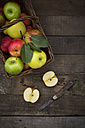 Different apples, basket and pocket knife on wood - LVF003842