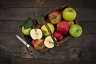 Different apples, basket and pocket knife on wood - LVF003845