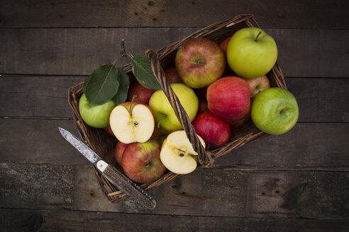 Different apples, basket and pocket knife on wood - LVF003845