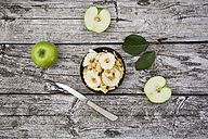 Bowl of apple chips, leaves, kitchen knife and two Granny Smith on wood - LVF003857
