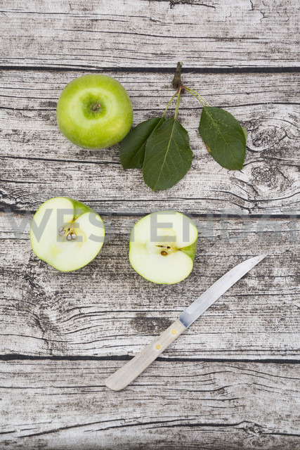 Sliced and whole Granny Smith, leaves and kitchen knife on wood - LVF003860 - Larissa Veronesi/Westend61