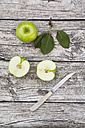 Sliced and whole Granny Smith, leaves and kitchen knife on wood - LVF003860