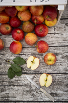 Whole and sliced red apples, leaves and a kitchen knife on wood - LVF003863