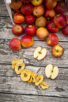 Whole and sliced red apples and apple chips on wood - LVF003866