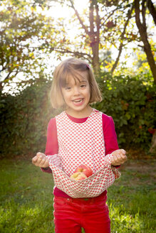 Portrait of little girl holding apples with her dress - LVF003873