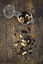 Mixed nuts and raisins in glass on wood - LVF003881