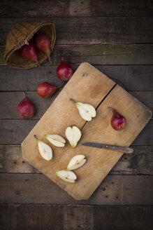 Whole and sliced organic red Clapp's Favourites, wooden board and kitchen knife on dark wood - LVF003903