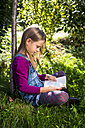 Little girl sitting on a meadow in the garden reading a book - SARF002110