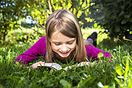 Little girl lying on a meadow in the garden reading a book - SARF002113