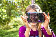 Little girl sitting on a meadow in the garden showing display of smartphone with her selfie - SARF002116
