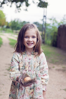 Smiling girl holding an egg in a nest - XCF000029