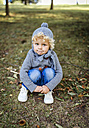 Portrait of little boy crouching on a meadow - MGOF000785