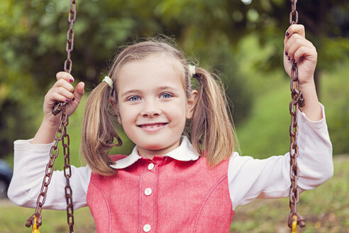 Portrait of smiling little girl with braids on a swing - XCF000034