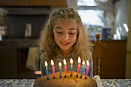 Portrait of little girl looking at candles on her birthday cake - RAEF000506