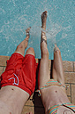 Italy, Brother and sister sitting at edge of a swimming pool, splashing water - LBF001212