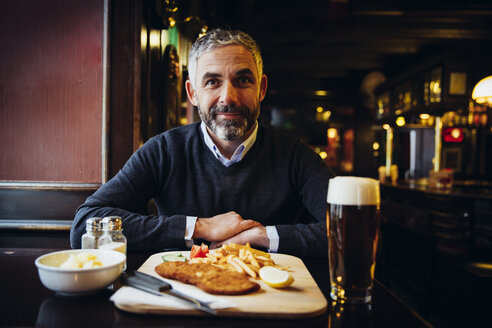 Smiling man in restaurant having Wiener Schnitzel with French fries - AIF000093
