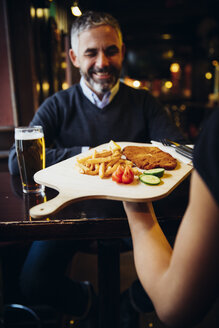 Smiling man in restaurant receiving Wiener Schnitzel with French fries - AIF000096