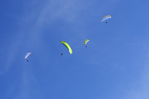 Austria, Tyrol, four paragliders in front of blue sky - JED000245