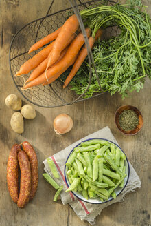 Ingredients for bean stew, carrots in basket, green beans in bowl, onion, potatoes and minced pork sausage on wood - ODF001344