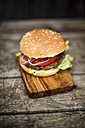 Homemade burger with lettuce, meat, tomato and onion on chopping board - SARF002134