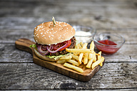 Homemade burger with lettuce, meat, tomato, onion and french fries on chopping board - SARF002137