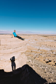 Chile, Atacama Desert, man sitting on a cliff with shadow of a photographer - GEMF000392