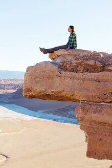 Chile, Atacama Desert, woman sitting on a cliff looking at view - GEMF000395