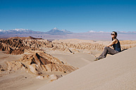 Chile, Atacama Desert, woman sitting on a dune looking at view - GEMF000398