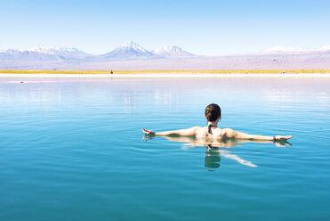 Chile, Atacama Desert, woman floating in the Laguna Cejar salt lake - GEMF000404
