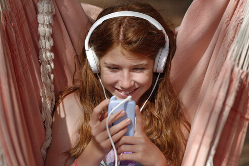 Portrait of girl with headphones and smartphone in a hammock - LBF001216