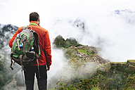 Peru, Machu Picchu region, Traveler looking at Machu Picchu citadel and Huayna mountain - GEMF000415