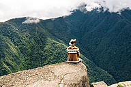 Peru, Machu Picchu region, man sitting on rock spur, looking at view - GEM000418