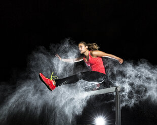 Young woman jumping over hurdle in between cloud of flour - STSF000944