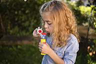 Blond little girl blowing soap bubble - RAEF000512