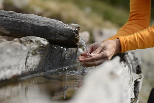 Hands scooping water from a well - LBF001219