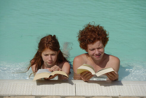 Redheaded girl and boy lying side by side in a swimming pool reading a book - LBF001221