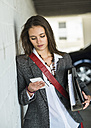 Young woman holding folder looking at cell phone - UUF005748