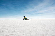 Bolivia, Potosi, man standing on his 4x4 in the Uyuni Salt Flats - GEMF000430