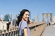 USA, New York City, portrait of smiling young woman on Brooklyn Bridge - GIOF000133