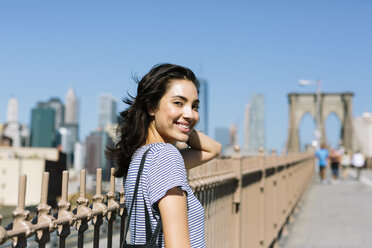USA, New York City, portrait of smiling young woman on Brooklyn Bridge - GIOF000133