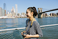 USA, New York City, smiling young woman with camera - GIOF000136