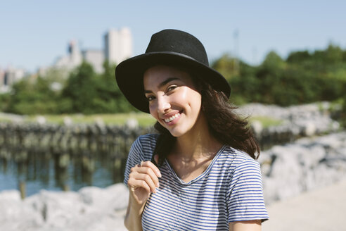 USA, New York City, portrait of smiling young woman wearing black hat - GIOF000142