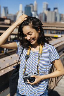 USA, New York City, portrait of smiling young woman with camera - GIOF000151
