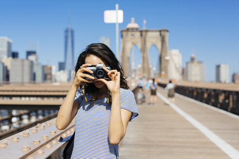 USA, New York City, young woman standing on Brooklyn Bridge taking a photo with camera - GIOF000154