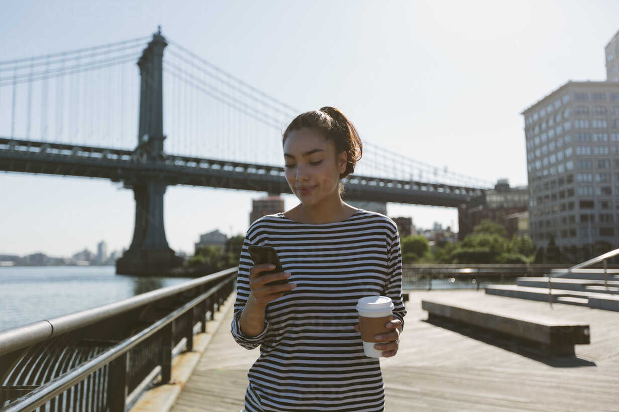 USA, New York City, portrait of smiling young woman with coffee to go looking at her smartphone - GIOF000157 - Giorgio Fochesato/Westend61