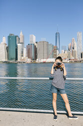 USA, New York City, young woman  taking a photo with camera in front of the skyline - GIOF000160