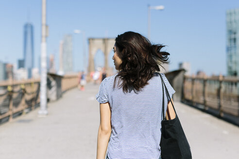 USA, New York City, back view of young woman walking on Brooklyn Bridge - GIOF000163