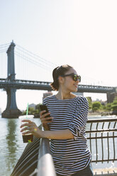 USA, New York City, smiling young woman with soft drink looking at smartphone - GIOF000169