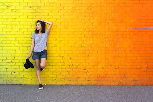 Young woman leaning against yellow brick wall - GIOF000172